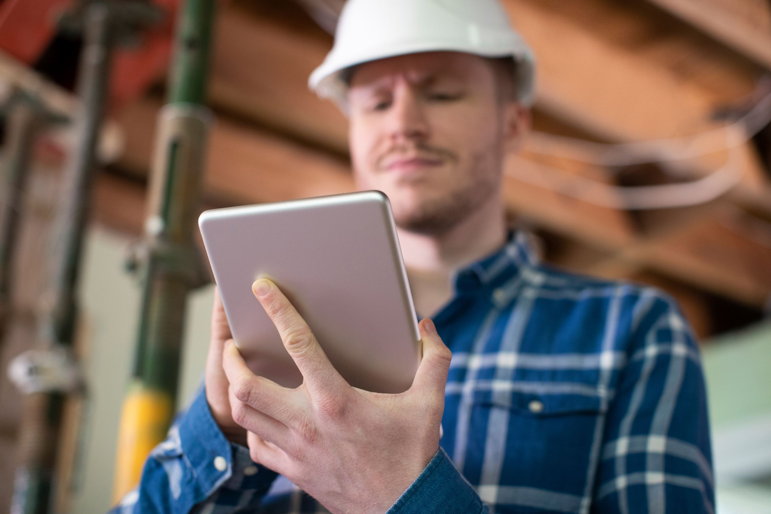 Contractor at Job Site Holding Tablet